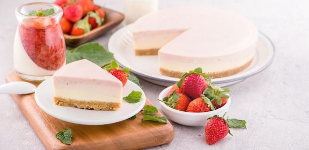 Délicieux et nutritif à la fraise à la main pas de cuisson au fromage de couleur dégradé congelé tranche de gâteau au fromage frais avec sarcocarpe cru en plus isolé avec un fond gris juste face, espace copie, gros plan
