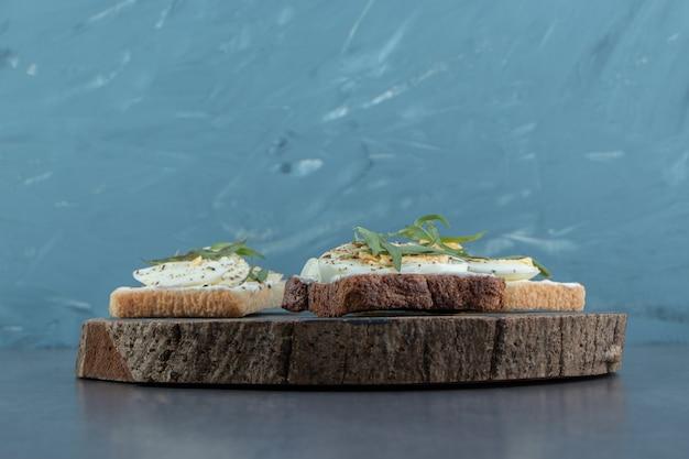 De délicieux œufs durs avec du pain grillé sur un morceau de bois.