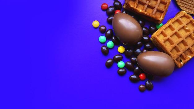Délicieux oeufs de pâques au chocolat, gaufres, bonbons sur fond bleu foncé