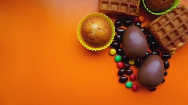 Délicieux oeufs de pâques au chocolat, gaufres, bonbons sur fond orange