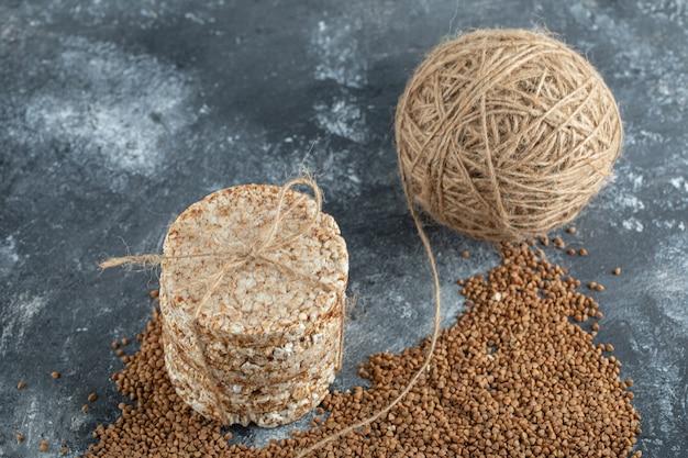 Délicieux pain croustillant, fil et sarrasin cru sur une surface en marbre