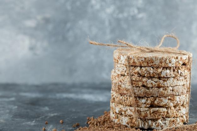 Délicieux pain croustillant et sarrasin cru sur une surface en marbre