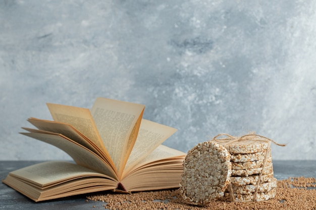 Délicieux pain croustillant, sarrasin non cuit et livre sur une surface en marbre