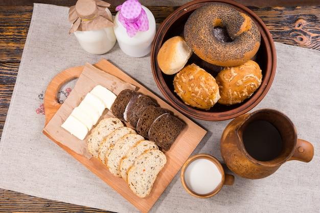 Délicieux pain et fromage pub déjeuner avec du pain de grains entiers en tranches et un bol de petits pains assortis servi avec des bouteilles de lait frais de la ferme, vue aérienne