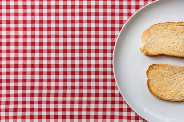 Délicieux pain grillé, servi sur une nappe à carreaux vintage.