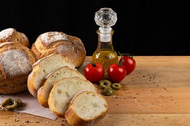 Délicieux pain italien sur socle en bois avec huile d'olive, tomates et olives sur fond noir