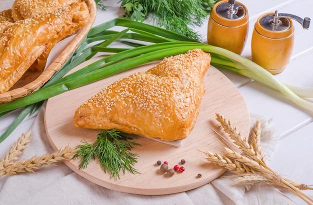 Délicieux pain de pâte feuilletée triangulaire frais aux graines de sésame farcies sur une planche de bois ronde sur fond de bois blanc
