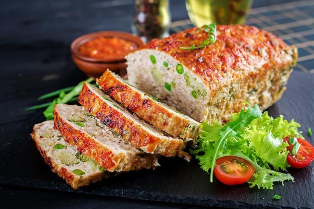 Délicieux pain de viande au poulet haché fait maison avec des pois verts et du brocoli sur tableau noir.