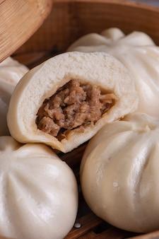 Délicieux pain de viande cuit à la vapeur chinois baozi est prêt à manger sur une assiette de service et un cuiseur à vapeur close up copy space product design concept