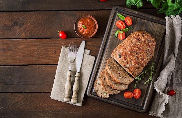 Délicieux pain de viande de dinde cuit au four sur une table en bois.