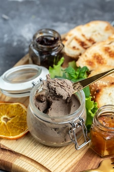Délicieux pâté de foie de canard avec des morceaux de pain blanc sur une planche de bois. apéritifs gourmands, assortiment de bruschettas apéritifs italiens