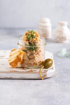 Délicieux pâté de poulet fait maison avec des épices et de l'aneth dans un bocal en verre et une tranche de pain à proximité et des câpres sur fond clair. mise au point sélective.