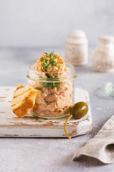 Délicieux pâté de poulet maison aux épices et à l'aneth dans un bocal en verre et une tranche de pain à proximité et câpres sur une table légère. mise au point sélective.