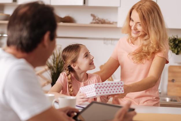 Délicieux père d'âge mûr joyeux profitant de vacances en famille à la maison et à l'aide de tablette tandis que femme donnant présent fort à l'enfant