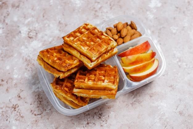 Délicieux petit déjeuner avec amandes, tranches de pommes rouges, gaufres, croissants sur boîte à lunch en plastique à la lumière