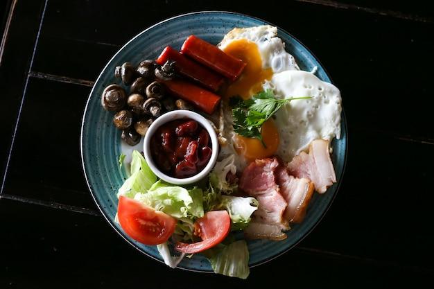 Délicieux petit déjeuner anglais avec des œufs au plat, des saucisses, des haricots, des champignons, des tomates et du bacon, vue de dessus