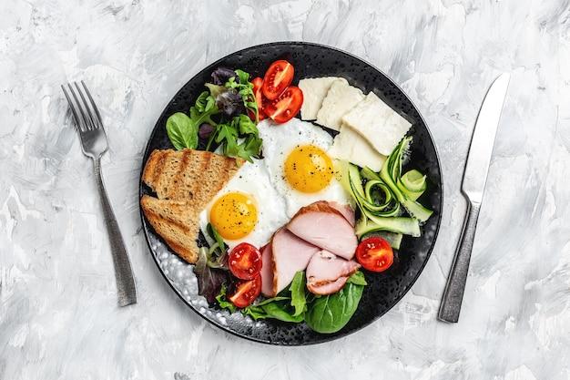 Délicieux petit déjeuner anglais. oeufs frits avec du pain grillé et du bacon. petit-déjeuner sain. vue de dessus.