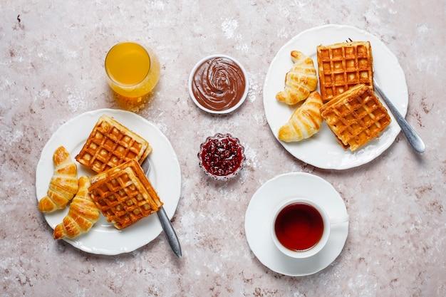 Délicieux petit déjeuner avec café, jus d'orange, gaufres, croissants, confiture, pâte de noix à la lumière, vue de dessus