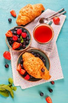 Délicieux petit déjeuner avec des croissants aux amandes fraîches, des baies et une tasse de thé sur un fond en bois bleu ciel