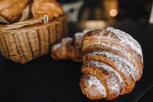 Délicieux petit déjeuner avec des croissants frais sur fond noir, une délicieuse cuisson vue de dessus copie espace pour le texte