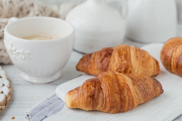 Délicieux petit-déjeuner avec des croissants frais et une tasse de café sur un bois blanc