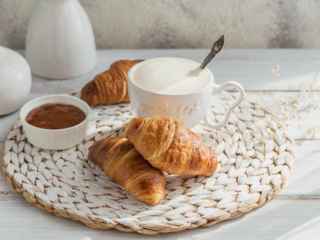 Délicieux petit-déjeuner avec des croissants frais et une tasse de café servi avec de la confiture sur un bois blanc. délicieuse pâtisserie