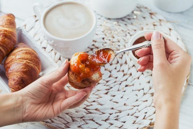 Délicieux petit-déjeuner avec croissants frais et tasse de café servi avec de la confiture sur un bois blanc