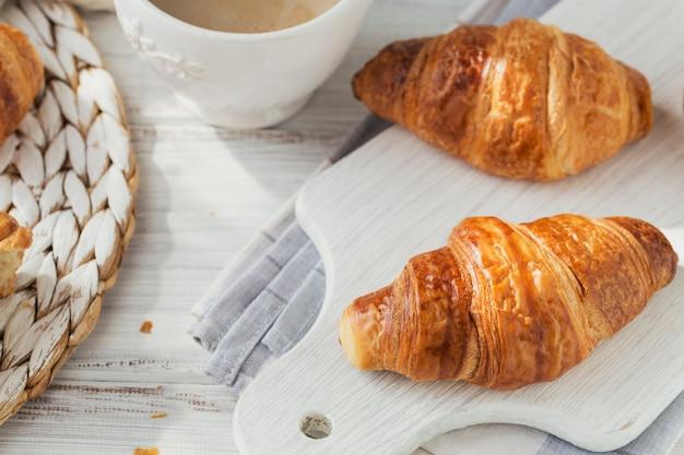 Délicieux petit-déjeuner avec des croissants frais et une tasse de café sur une table en bois blanc