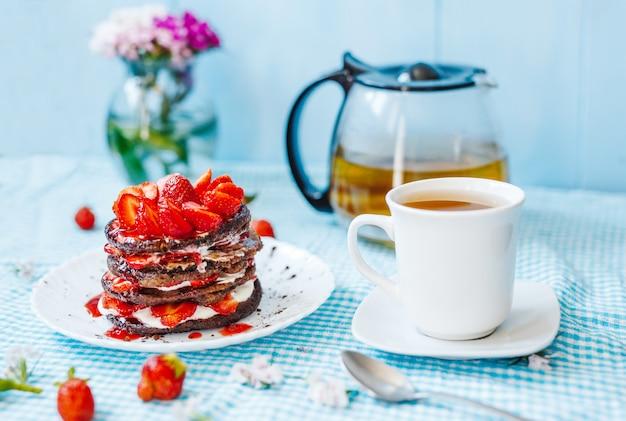 Délicieux petit déjeuner désert. pile de crêpes aux fruits et confiture de fraises et thé, en plaque blanche sur une table bleue.