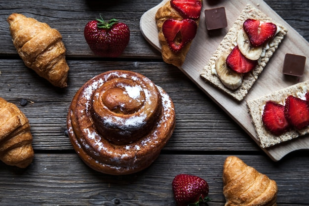 Délicieux petit déjeuner avec des fraises et des petits pains sucrés sur bois. fruits, nourriture, chocolat