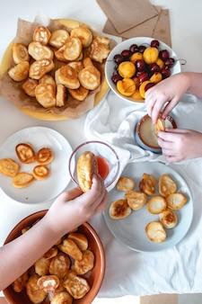 Délicieux petit déjeuner avec de minuscules mini crêpes confiture de cerises abricots