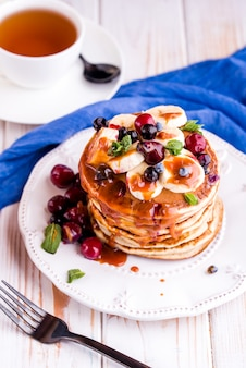 Délicieux petit-déjeuner sain et copieux sur le tableau blanc. crêpes aux fruits, jus d'orange. haut