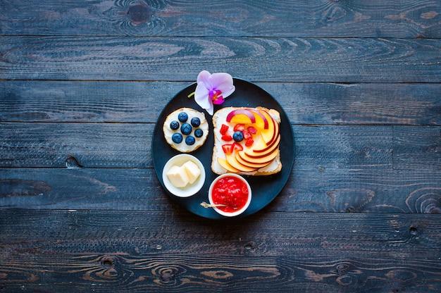 Délicieux petit-déjeuner sain, sandwichs aux fruits avec différentes garnitures, fromage, banane, fraise, pêche, beurre, myrtille, sur une surface en bois différente.