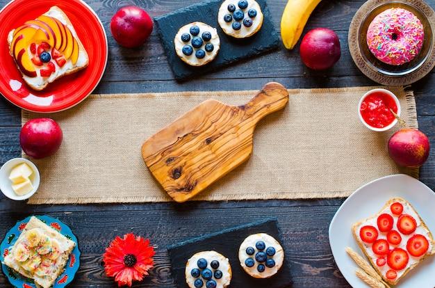 Délicieux petit déjeuner sain, sandwichs aux fruits avec différentes garnitures, fromage, banane, fraise, pêche, beurre, myrtille, sur une table en bois différente