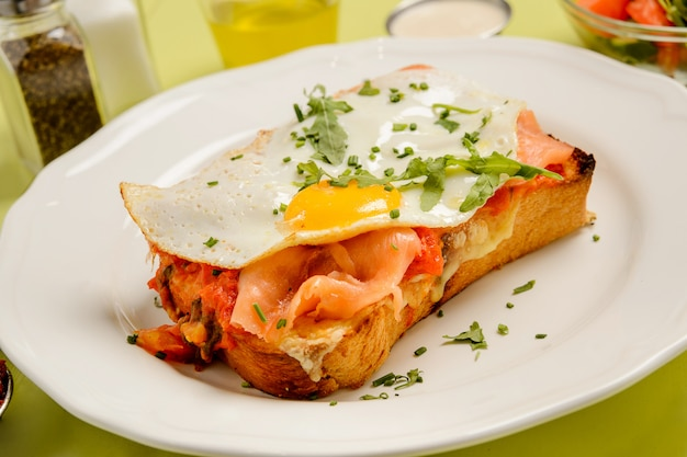 Délicieux petit déjeuner. toast au saumon, oeuf et légumes