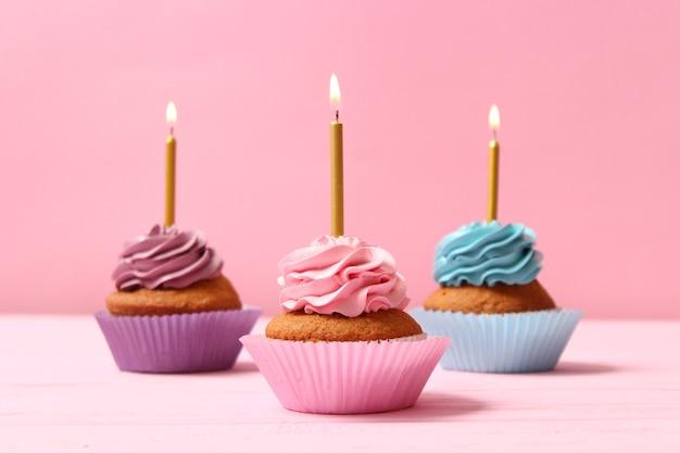 Délicieux petit gâteau avec une bougie sur un fond coloré avec un espace pour insérer du texte. contexte festif, anniversaire. photo de haute qualité