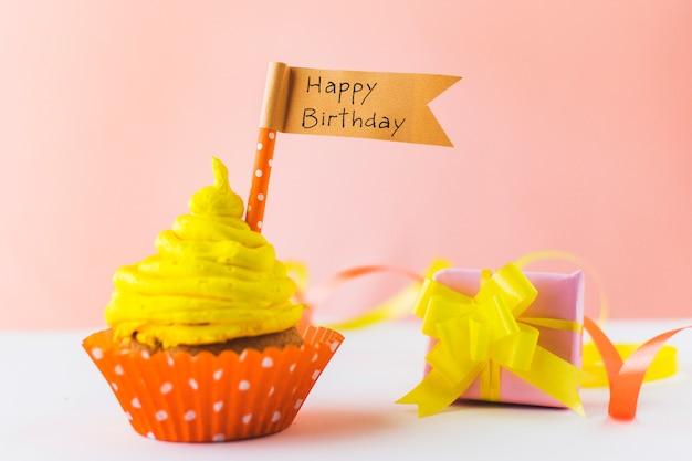 Délicieux petit gâteau avec un drapeau de joyeux anniversaire près d'un cadeau sur une surface blanche