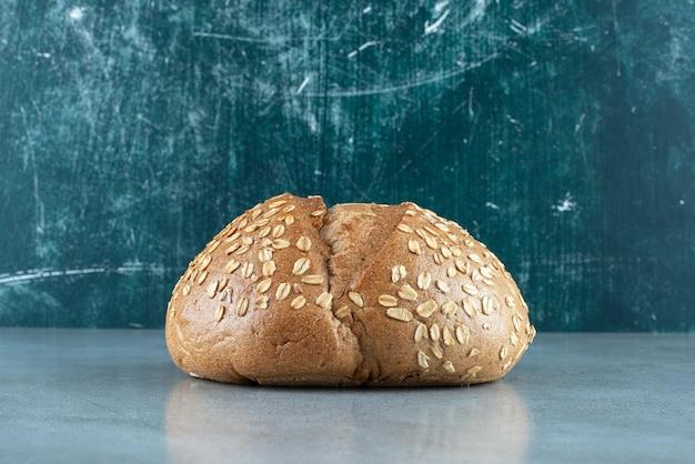 Délicieux petit pain aux graines sur marbre.