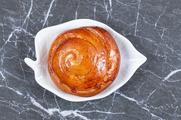 Délicieux petit pain sur le bol, sur la surface en marbre
