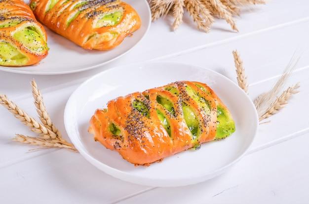 Délicieux petit pain frais avec remplissage de kiwi sur plaque blanche sur fond de bois blanc