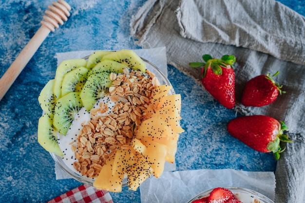 Délicieux petits déjeuners de yaourts aux fruits, muesli, chia et sirop.