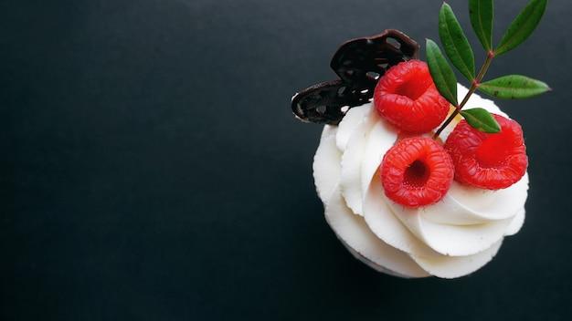 Délicieux petits gâteaux aux framboises sur une surface sombre - dessert sucré fait main, cupcake à la crème au beurre et framboise