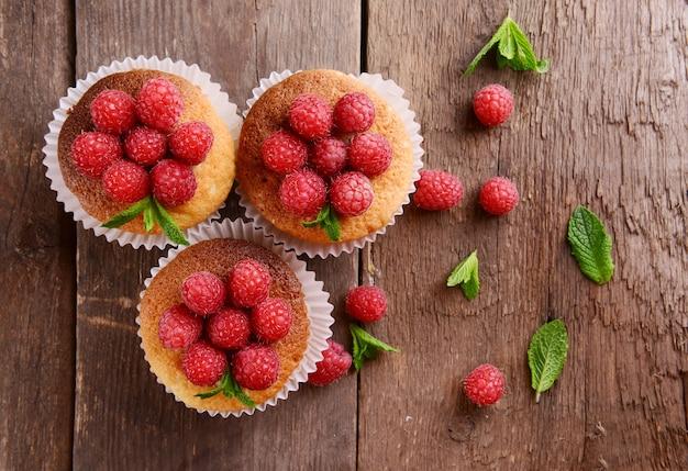 Délicieux petits gâteaux aux fruits rouges et menthe fraîche sur la table en bois se bouchent