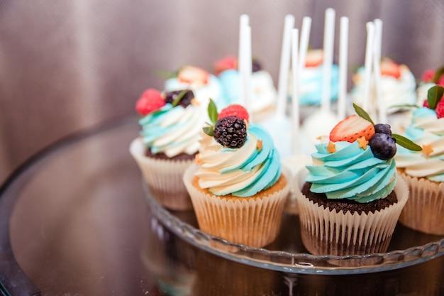 Délicieux petits gâteaux aux petits fruits petits gâteaux à la vanille avec crème de bleuets et petits fruits. fermer. mise au point sélective concept de restauration de luxe cupcakes à la crème de fromage