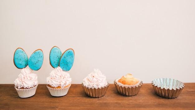 De délicieux petits gâteaux avec de la crème blanche et des cakepops bleus en ligne placés sur une surface en bois