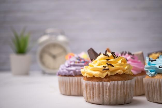 De délicieux petits gâteaux faits maison avec de la crème colorée et garniture de bonbons et de biscuits au chocolat.