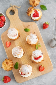 Délicieux petits gâteaux faits maison profiterole choux avec crème anglaise, fraise et poudre de glaçage sur fond de béton gris. espace de copie.