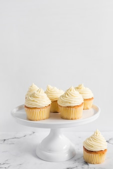 Délicieux petits gâteaux sur un gâteau debout sur une table en marbre sur fond blanc