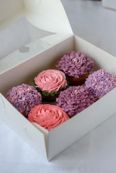 Délicieux petits gâteaux multicolores dans une boîte blanche sur fond blanc.
