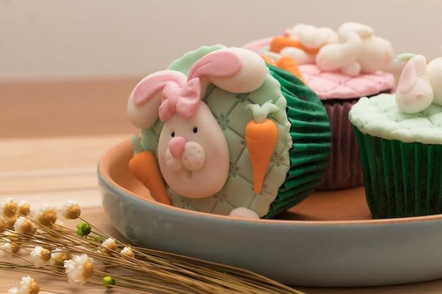 Délicieux petits gâteaux de pâques sur une assiette rustique et fond en bois